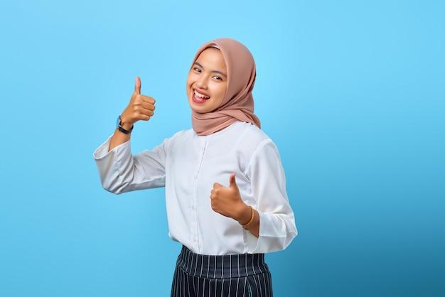 Retrato de uma jovem asiática alegre e animada mostrando os polegares para cima ou um sinal de aprovação