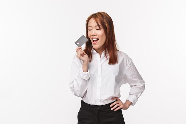 Retrato de uma jovem asiática bem-sucedida e satisfeita, segurando o cartão de crédito, sorrindo e parecendo satisfeito, foi pago, comprando algo que queria, fazer pedido, de pé na parede branca
