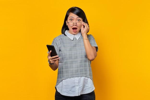 Retrato de uma jovem asiática chocada e surpresa segurando um smartphone e óculos, olhando para a câmera sobre fundo amarelo