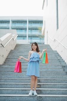 Retrato de uma jovem asiática descendo as escadas com uma sacola de compras colorida