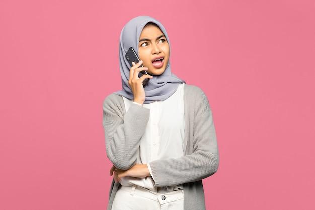 Retrato de uma jovem asiática espantada conversando com amigos no celular