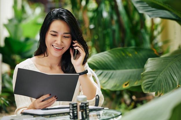 Retrato de uma jovem asiática feliz lendo catálogo, falando ao telefone e pedindo ingredientes para sua marca de cosméticos