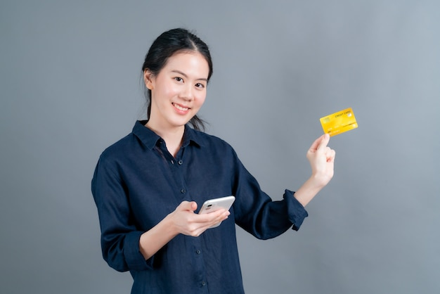 Retrato de uma jovem asiática feliz mostrando um cartão de crédito de plástico enquanto segura um telefone celular