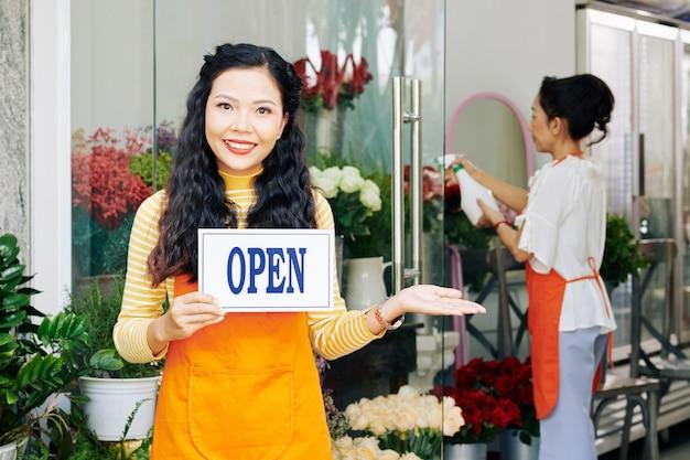 Retrato de uma jovem asiática feliz segurando uma placa aberta ao convidar um cliente em sua loja de flores