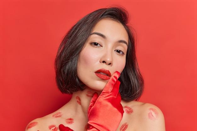 Retrato de uma jovem asiática gentil com pele limpa e saudável olha com ternura para a câmera e poses naturais de cabelo escuro para capa de revista parecem sedutoras isoladas sobre a parede vermelha do estúdio