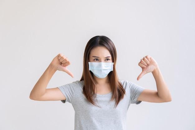 Retrato de uma jovem asiática infeliz com máscara protetora, polegares para baixo, posando sobre branco