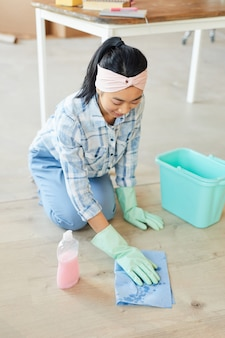 Retrato de uma jovem asiática limpando o chão de uma casa ou apartamento novo depois de se mudar