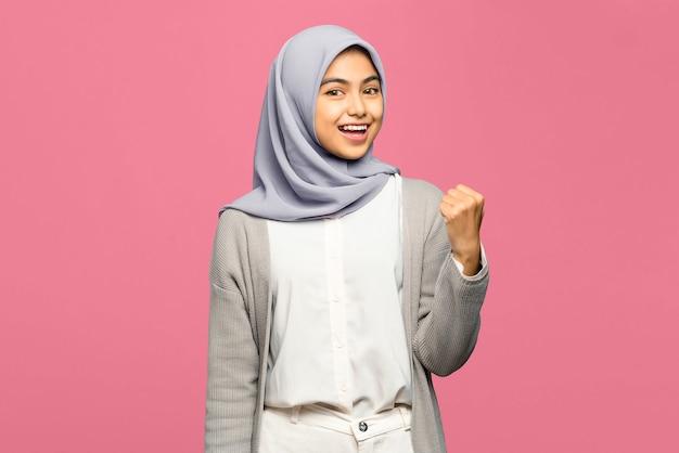 Retrato de uma jovem asiática muito feliz com a mão levantada