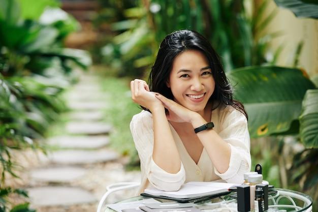 Retrato de uma jovem asiática sorridente e atraente, sentada à mesa no quintal e trabalhando no plano de negócios para sua marca de cosméticos