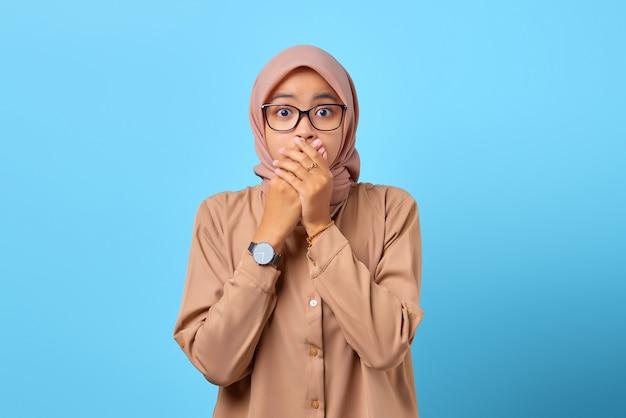 Retrato de uma jovem asiática surpresa, cobrindo a boca com a mão por engano Foto Premium