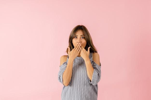Retrato de uma jovem asiática surpresa. ela tem olhos grandes e usa as mãos para cobrir a boca
