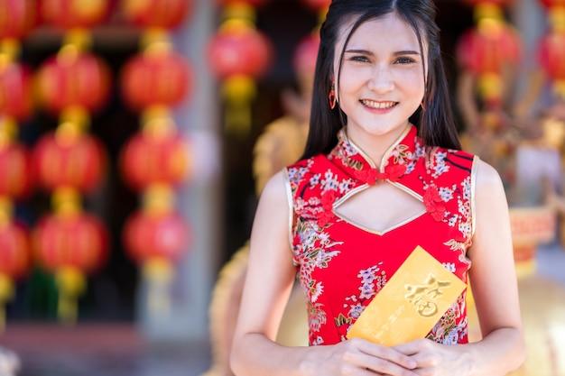Retrato de uma jovem asiática vestindo um cheongsam chinês tradicional vermelho, segurando envelopes amarelos com o texto chinês bênçãos escrito é uma boa sorte para o festival de ano novo chinês