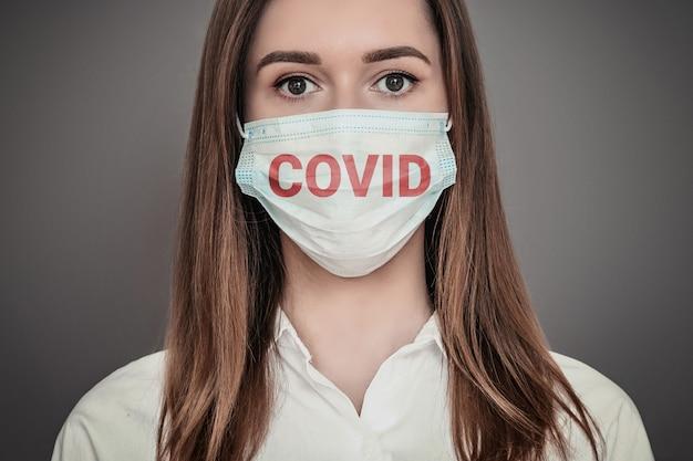 Retrato de uma jovem assustada, vestindo uma máscara respiratória médica com palavra secreta, isolada em uma parede cinza escura