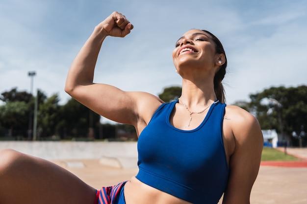 Retrato de uma jovem atleta sorrindo e mostrando seu bíceps ao ar livre.