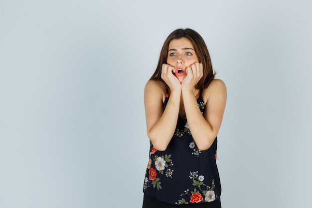Retrato de uma jovem atraente apoiando-se nas mãos na blusa e olhando a vista frontal apavorada