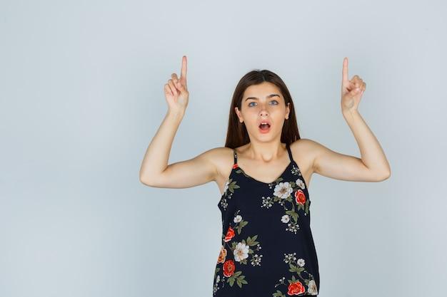 Retrato de uma jovem atraente apontando para cima com a blusa e olhando maravilhado para a vista frontal