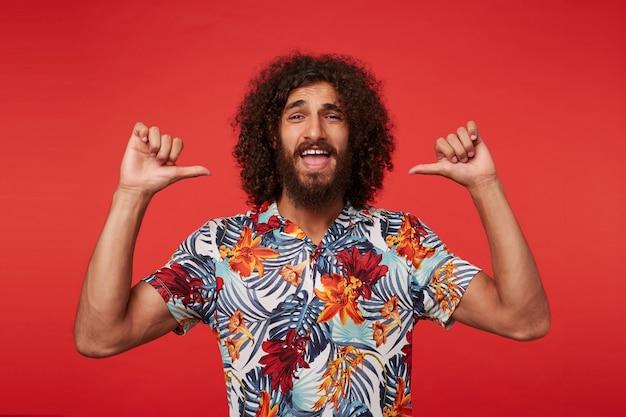 Retrato de uma jovem atraente barbudo com cabelo castanho cacheado, olhando para a câmera com alegria e apontando para si mesmo com autoconfiança com os polegares levantados, isolado sobre um fundo vermelho