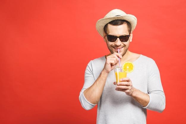 Retrato de uma jovem atraente com chapéu e óculos escuros em pé e bebendo suco de laranja sobre fundo vermelho
