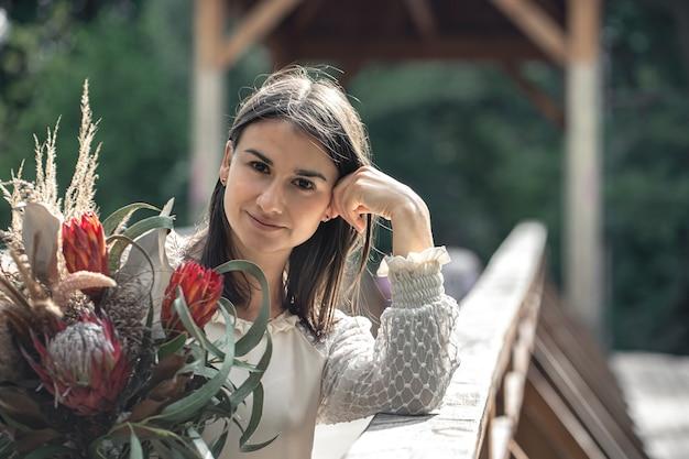 Retrato de uma jovem atraente com um buquê de flores exóticas, um buquê com flores protea.