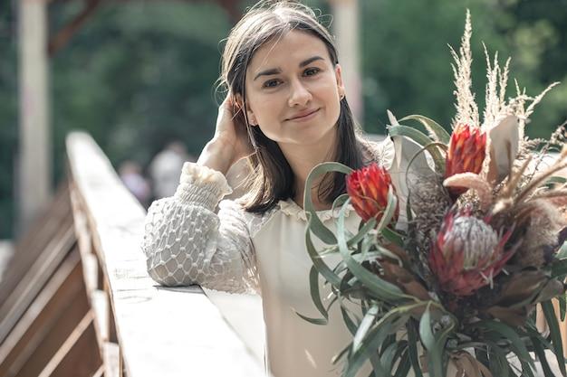 Retrato de uma jovem atraente com um buquê de flores exóticas