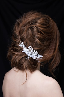 Retrato de uma jovem atraente com um penteado de casamento. vista traseira.