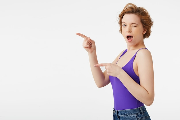 Retrato de uma jovem atraente de cabelos curtos, vestindo uma camisa roxa e jeans, sorrindo amplamente, piscando e olhando, aponta o dedo para o espaço da cópia isolado sobre a parede branca.