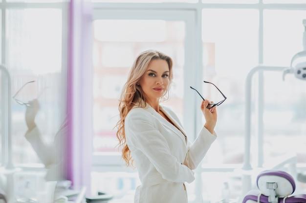 Retrato de uma jovem atraente dentista com cabelo longo cacheado em uniforme médico branco, posando com óculos contra grande janela no armário.