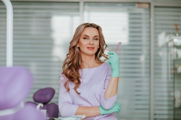Retrato de uma jovem atraente dentista com cabelo longo cacheado, em uniforme médico violeta e luvas médicas verdes, posando com ferramentas no armário