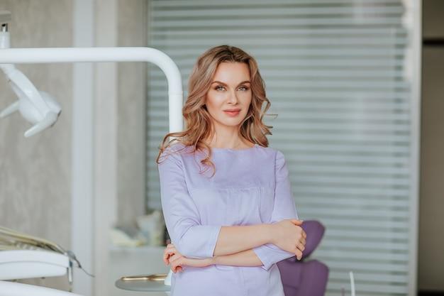Retrato de uma jovem atraente dentista com cabelo longo cacheado em uniforme médico violeta, posando no gabinete.