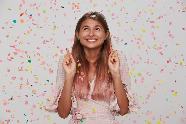 Retrato de uma jovem atraente e feliz com cabelo longo tingido de rosa pastel e vestido de bolinhas rosa apontando para cima