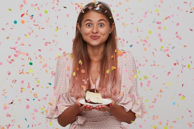 Retrato de uma jovem atraente e feliz com cabelo longo tingido de rosa pastel, usando um vestido rosa de bolinhas e comendo bolo