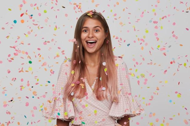 Retrato de uma jovem atraente e feliz com cabelo longo tingido de rosa pastel, usando um vestido rosa de bolinhas e tendo a festa isolada na parede branca com confete