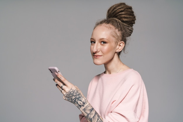 Retrato de uma jovem atraente e sorridente com dreadlocks, isolado, segurando um telefone celular