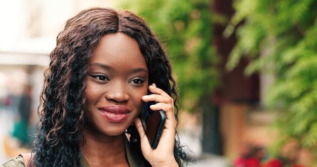 Retrato de uma jovem atraente falando smartphone ao ar livre bela garota multirracial usando ...