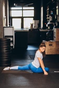 Retrato de uma jovem atraente fazendo exercícios de ioga ou pilates