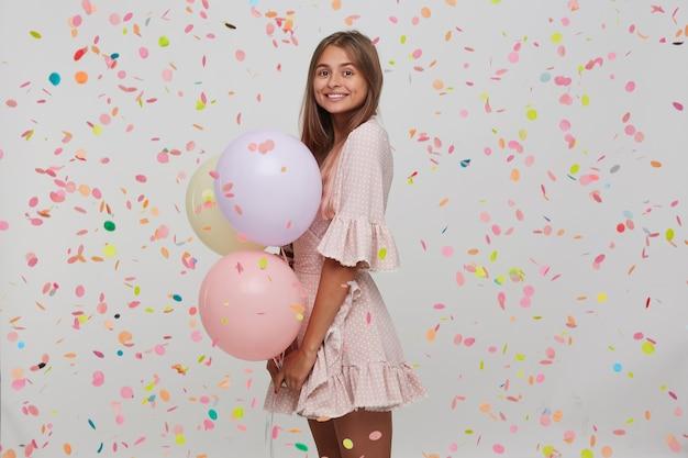 Retrato de uma jovem atraente feliz com cabelo longo tingido de rosa pastel usa um vestido rosa de bolinhas segurando balões coloridos na mão e tendo uma festa isolada na parede branca com