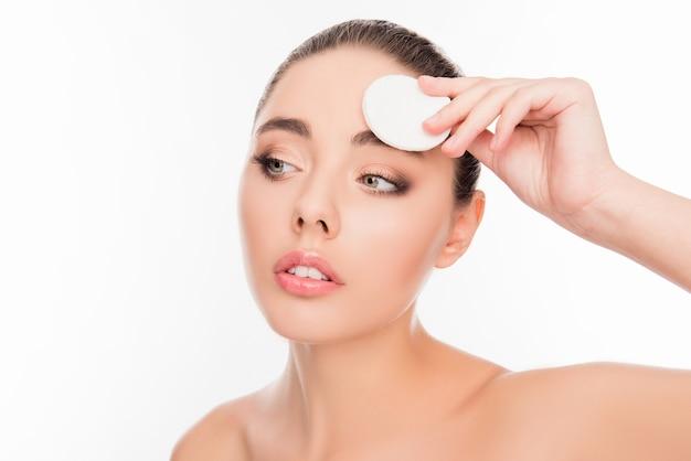 Retrato de uma jovem atraente lavando a maquiagem com uma almofada de algodão