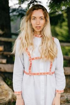 Retrato de uma jovem atraente loira sensível em um vestido branco com ornamento posando sobre fundo de natureza
