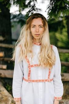 Retrato de uma jovem atraente loira sensível em um vestido branco com ornamentos posando sobre a natureza