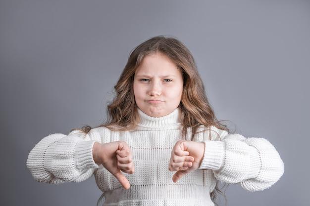 Retrato de uma jovem atraente menina com cabelos loiros no suéter insatisfeito cético, mostrando os polegares para baixo, antipatia, sinal de desaprovação com as duas mãos sobre um fundo cinza do estúdio.