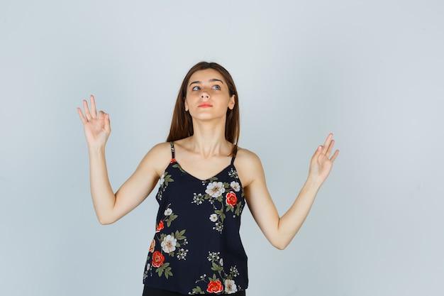 Retrato de uma jovem atraente mostrando um gesto de ioga na blusa e olhando esperançoso de frente