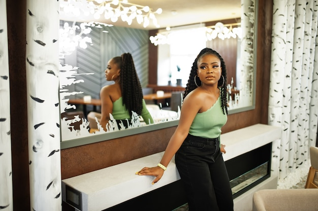 Retrato de uma jovem atraente mulher afro-americana, vestindo uma camisola verde e calça jeans preta posar contra o espelho.
