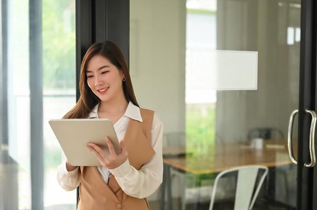 Retrato de uma jovem atraente segurando seu tablet digital enquanto trabalhava em um escritório moderno.