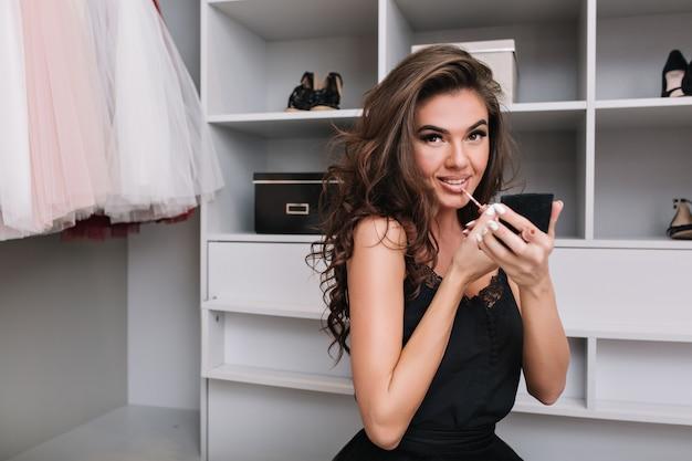 Retrato de uma jovem atraente sentada no camarim e faz maquiagem, com batom na mão. ela se vestiu com uma roupa elegante cercada por roupas.