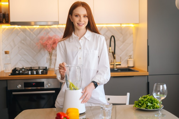 Retrato de uma jovem atraente sorridente fazendo suco de smoothie de desintoxicação de vegetais saudáveis no liquidificador