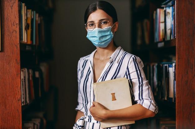 Retrato de uma jovem atraente universitária em pé na biblioteca com uma máscara facial, segurando um livro