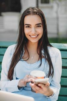 Retrato de uma jovem atraente usando um smartphone enquanto bebia café sentado em uma praia no parque com um laptop nas pernas olhando para a câmera sorrindo