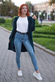 Retrato de uma jovem, bela e atraente ruiva caucasiana com sardas. garota posando andando pela cidade.