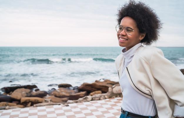 Retrato de uma jovem bela mulher latina, desfrutando de um ar fresco com o mar na.