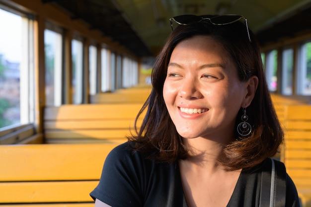 Retrato de uma jovem bela turista asiática andando de trem na estação ferroviária hua lamphong